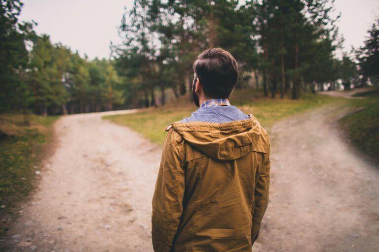 Person som står vid ett vägskäl.