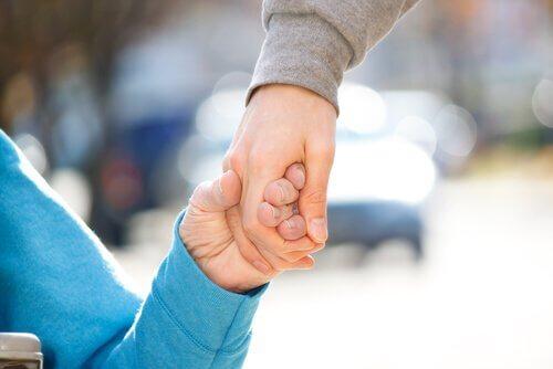 barn och vuxen som håller hand