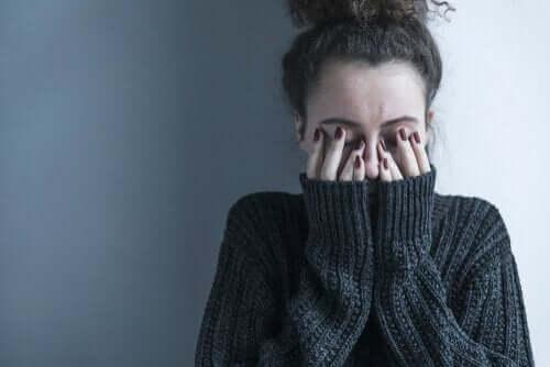 Kvinna med händerna för ögonen.