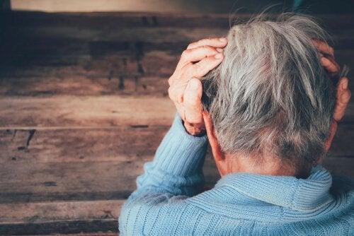 Äldre person med händerna på huvudet.