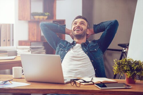 En glad man sitter vid ett skrivbord.