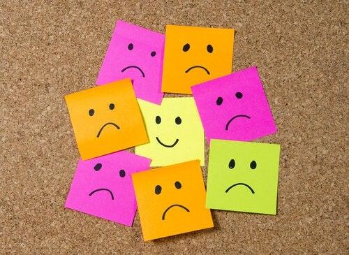 Post-it-lappar med ett tecknat glatt ansikte omgivet av ledsna ansikten. Representerar en positiv inre dialog.