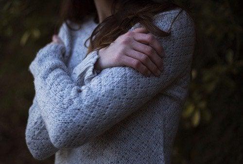 En kvinna omfamnar sig själv under känslomässig detox.