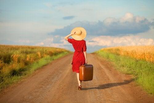 En kvinna med en resväska som går på en väg.