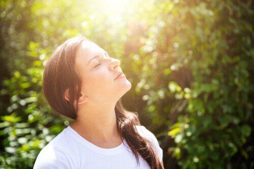 Kvinna som andas djupt i naturen