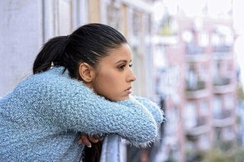 Kvinna som blickar ut från sin balkong