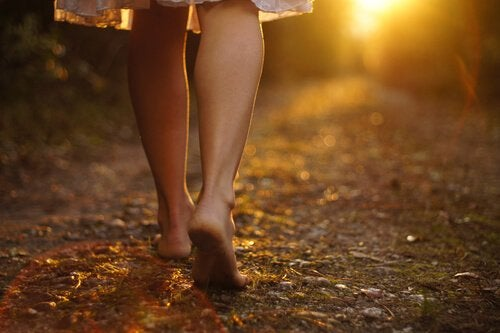 Kvinna som går på gräs.