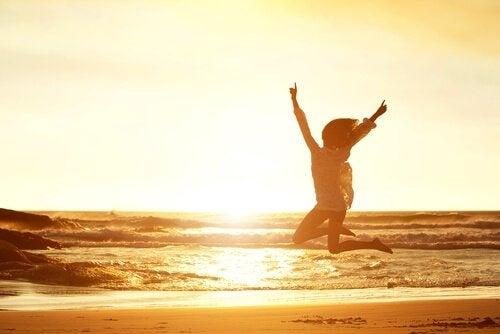 Kvinna som hoppar på stranden.