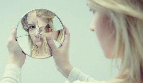En kvinna tittar på sig själv i en trasig spegel.