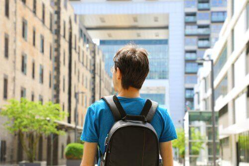 Man med ryggsäck som vandrar i en stad