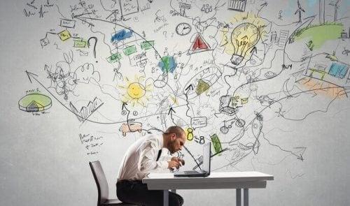 En man som sitter och arbetar vid ett skrivbord.