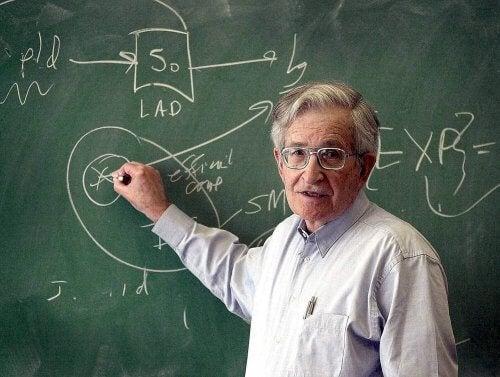 Noam Chomsky står och skriver vid en griffeltavla.