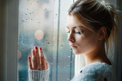 Ledsen kvinna vid fönster