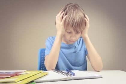Koncentrerad skolpojke med händerna för tinningarna