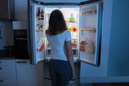 En kvinna som tittar i sitt kylskåp.