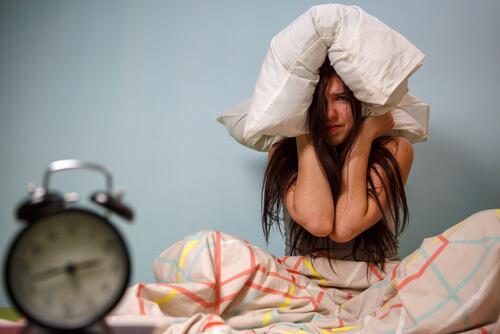 Kvinna som håller kudde för huvudet.