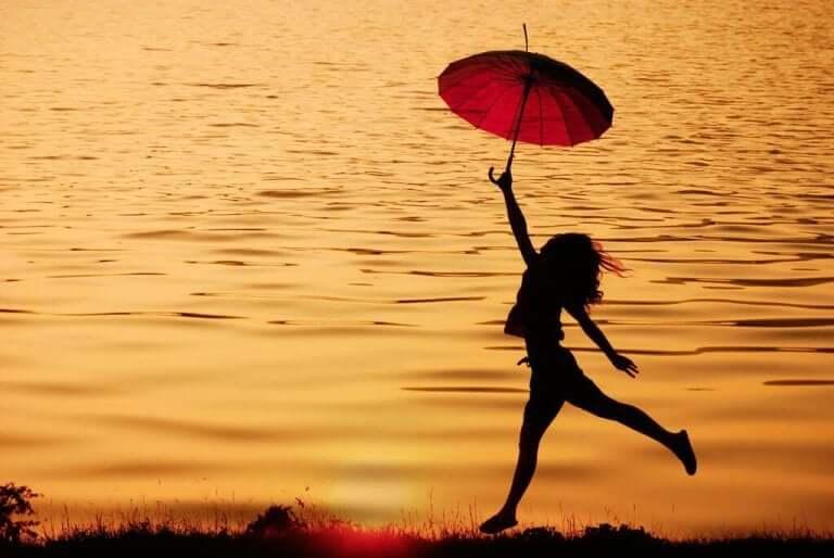 Kvinna som hoppar vid vattnet.