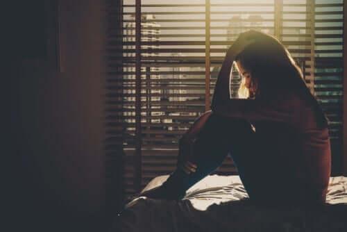 Kvinna som sitter på sängen.