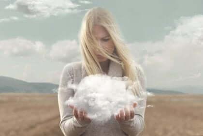 Kvinna som står på en åker med ett moln i sina händer
