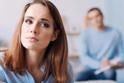 Ledsen kvinna med partner i bakgrunden
