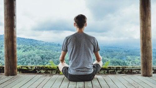 Man som mediterar bland bergen.