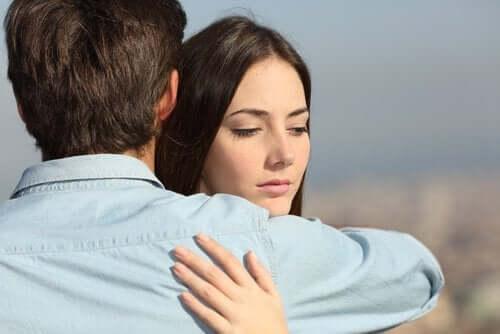 En misstänksam kvinna som kramar sin partner.