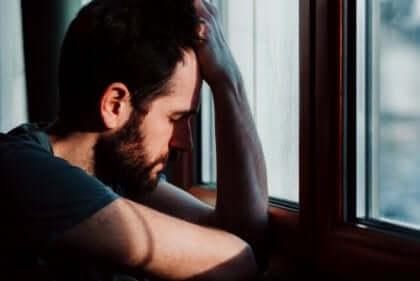 Orolig man som lutar sig mot en fönsterbräda