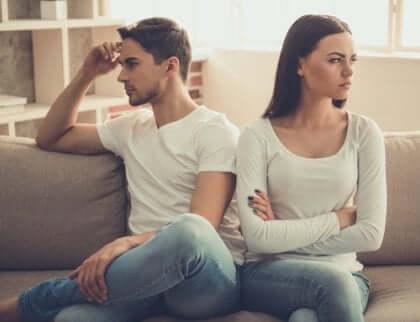 Par som sitter på soffan med ryggarna vända mot varandra