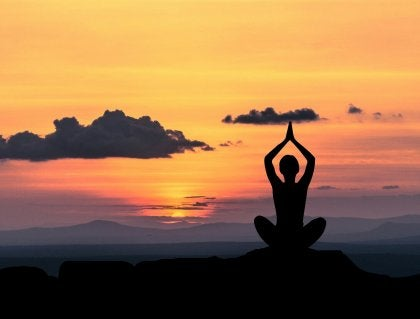 Person som mediterar i solnedgången mot förväntansångest