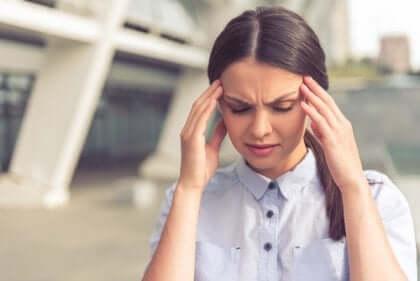 Stressad kvinna med händerna för tinningarna