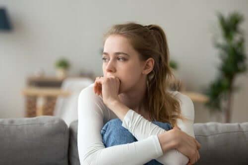 Fundersam kvinna som sitter i soffan med uppdragna ben