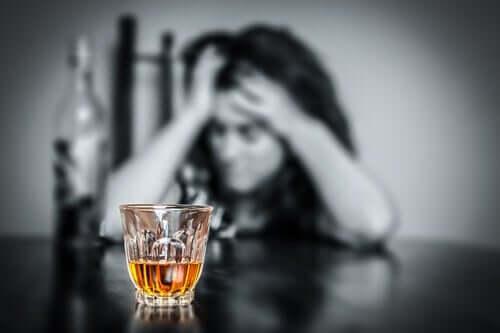 Deprimerad kvinna med ett spritglas i förgrunden