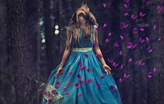Kvinna som är omgiven av fjärilar.