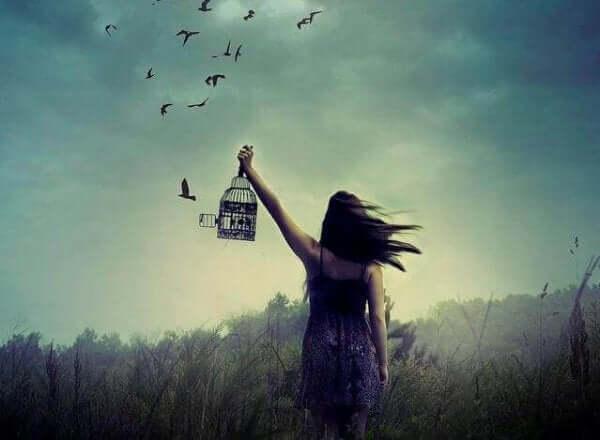 Kvinna som öppnar buren för fåglar.