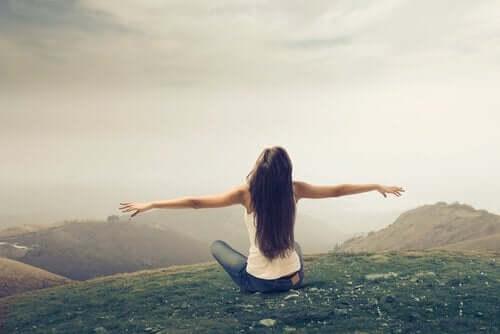 Kvinna som sitter på kulle.