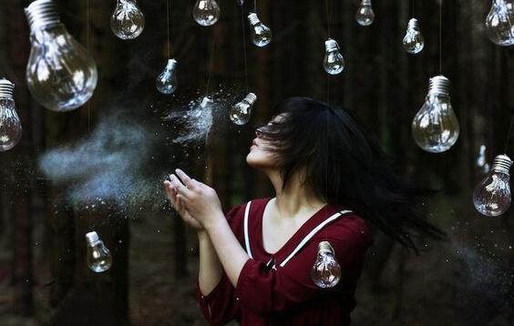 Kvinna som står bland glödlampor.
