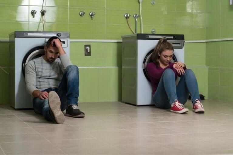 Par som sitter vid tvättmaskiner.