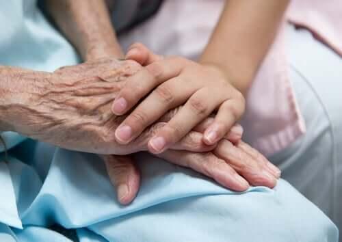 Vårdgivare som vilar handen på sin patients händer
