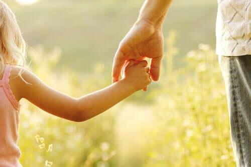 En vuxen som håller ett barn i handen