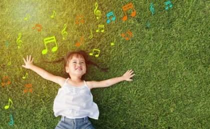 En liten flicka som ligger på gräset och lyssnar på musik.