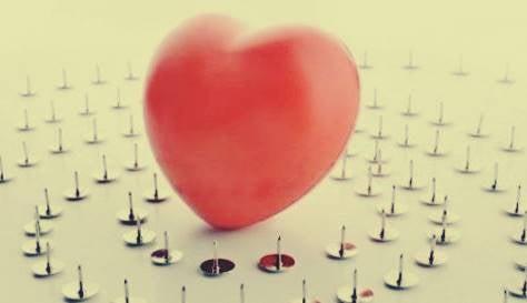 En hjärtformad ballong som är omgiven av häftstift.