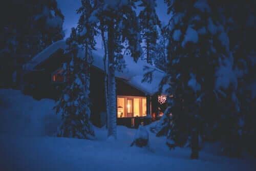 Hus med snö i skogen.