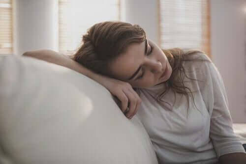 Kvinna som lutar sig mot soffa.