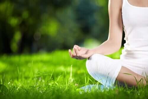 Kvinna som mediterar i gräset.