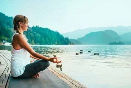Kvinna som mediterar vid sjö.
