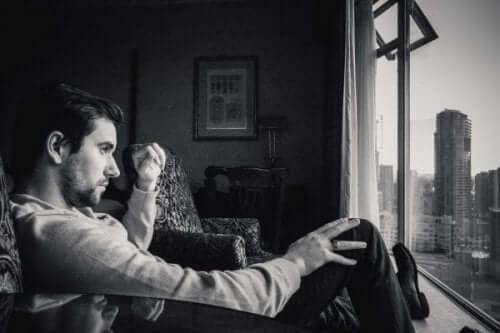 Man som tittar ut genom fönster.