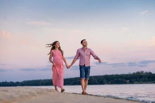 Ett par som går tillsammans på en strand.