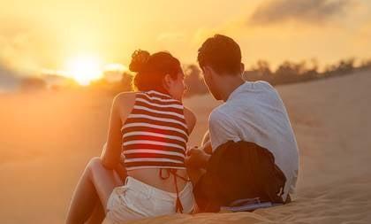 Par som sitter i sanden.