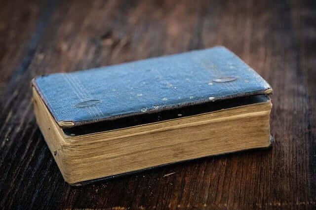 Gammal bok som ligger på bord.