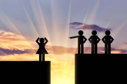 Tre manliga figurer som står på en plattform ovanför en kvinna och pekar ned på henne.